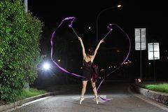 Asian girls dancing ballet on the road at night stock photography