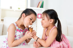 Asian girls eating ice cream. Eating ice cream. Asian girls sharing an ice cream. Beautiful children model at home stock photography