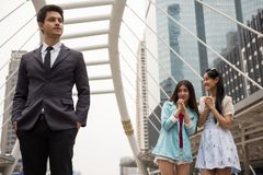 Asian girls look at handsome businessman. Beautiful Asian friends look and love at first sight at handsome businessman in modern city. Chinese women happy to see stock photos