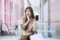 Asian girls with shopping bags using smartphone. Royalty Free Stock Images