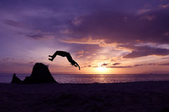Asian girls somersault on the beach. Asian girls somersault on the beach with purple sky sunrise Stock Photos