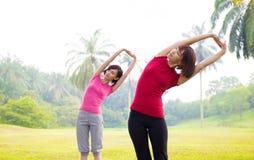 Asian girls streching outdoor. Two Asian girls stretching outdoor green park stock photos