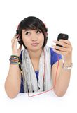 Asian girls think of a song. From his cell phone, on white background Stock Photo