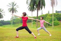 Asian girls yoga outdoor. Asian girls practicing yoga outdoor green park royalty free stock photos