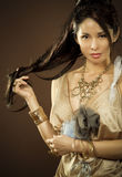 Asian glamour woman. Beautiful asian brunette wearing jewellery and fashin dress on dark background Stock Images