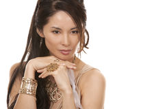Asian glamour woman. Beautiful asian brunette wearing jewellery and fashin dress on white background Royalty Free Stock Image
