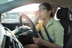 Asian business woman having headache. Asian glasses business woman having headache from migraine while driving a car with bad traffic jam on rush hours. Illness Stock Photos