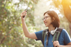 Asian glasses woman hiker with backpack taking nature photo with Stock Photo