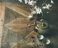 Asian golden iron teapot, cups, candles and almond blossom flowers. Traditional Asian tea ceremony arrangement. Golden iron teapot, cups, candles and almond Royalty Free Stock Photography