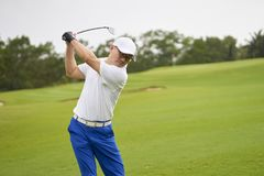 Asian man swinging club for tee-off in course. Asian golfer swinging club for tee-off in course in summer royalty free stock images