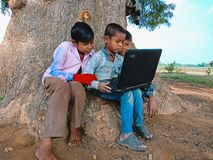 asian government school kids learning about laptop computer system at natural background in india January 2020