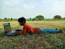 asian school kids learning about laptop computer system at natural green grass background in india January 2020