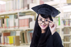 Asian graduate in graduation gown pose at library royalty free stock photography