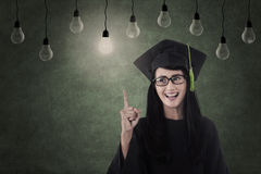 Asian graduate under light bulbs in classroom Royalty Free Stock Photography