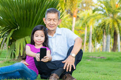 Asian grandfather and grandchild taking selfie with smartphone. In the park royalty free stock image