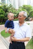 Asian grandfather holding grandson royalty free stock images