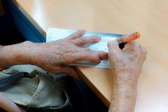 Asian grandma sign name in deposit Stock Images