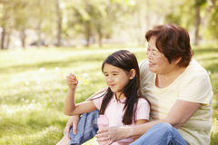 Asian grandmother and granddaughter blowing bubbles in park Stock Photos