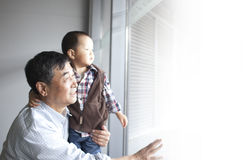 Asian grandpa hug grandson looking outside Stock Image