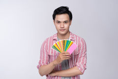 Asian graphic designer holding color palette over gray background. stock photos