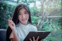 Asian girl`s business style hold a pen and smiling emotion positive thing of the day stock image