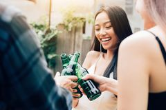 Asian group enjoying toasting drinks party with clinking beer bo royalty free stock images