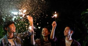 Asian group of friends having outdoor garden barbecue laughing w. Ith alcoholic beer drinks and showing group of friends having fun with sparklers on night ,soft royalty free stock photos