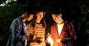 Asian group of friends having outdoor garden barbecue laughing w. Ith alcoholic beer drinks and showing group of friends having fun with sparklers on night ,soft stock images