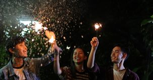 Asian group of friends having outdoor garden barbecue laughing w. Ith alcoholic beer drinks and showing group of friends having fun with sparklers on night ,soft royalty free stock image