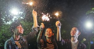 Asian group of friends having outdoor garden barbecue laughing w. Ith alcoholic beer drinks and showing group of friends having fun with sparklers on night ,soft Royalty Free Stock Images