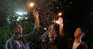 Asian group of friends having outdoor garden barbecue laughing w. Ith alcoholic beer drinks and showing group of friends having fun with sparklers on night ,soft royalty free stock photo