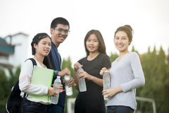 Asian Group of students sharing with the ideas for working  and. Holding water bottle on the campus lawn Stock Images