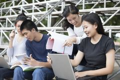 Asian Group of students using tablet and notebook sharing with t royalty free stock images