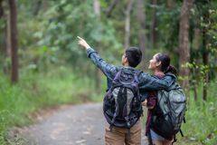 Asian Group of young people Hiking with friends backpacks walking together and looking map and taking photo camera by the road. And looking happy ,Relax time on stock images