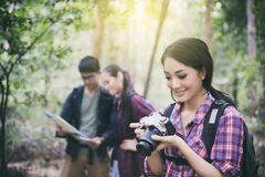 Asian Group of young people Hiking with friends backpacks walking together and looking map and taking photo camera by the road. And looking happy ,Relax time on royalty free stock images