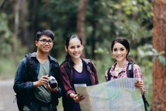 Asian Group of young people Hiking with friends backpacks walking together and looking map and taking photo camera by the road. And looking happy ,Relax time on stock photography