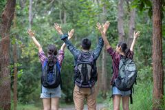 Asian Group of young people Hiking with friends backpacks walking together and looking map and taking photo camera by the road. And looking happy ,Relax time on stock photo