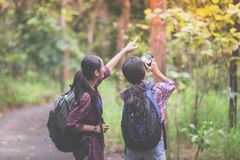 Asian Group of young people Hiking with friends backpacks walking together and looking map and taking photo camera by the road. And looking happy , Relax time stock photos