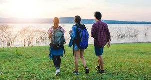Asian Group of young people Hiking with friends backpacks walking together and looking map and taking photo camera by the road and. Looking happy ,Relax time on stock photos