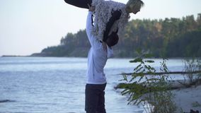 Asian guy lifts his caucasian girlfriend above his head on the background of a lake and forest. Teenagers in casual wear stock footage