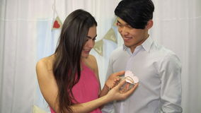 Asian guy presents Valentine card with a wedding ring to young girl stock video