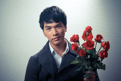 Asian guy with red roses in retro style. For valentine day stock photography