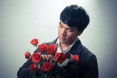 Asian guy with red roses in retro style Royalty Free Stock Photos