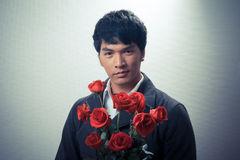 Asian guy with red roses in retro style Royalty Free Stock Image