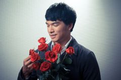 Asian guy with red roses in retro style Royalty Free Stock Images