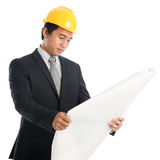 Asian guy with safety helmet and blue prints Stock Photo