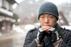The Asian guy with snow hat stare into the camera and thinking something, Shirakawako valley in the snow season background. The Asian guy with snow hat stare stock photos