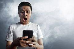 Asian guy surprised on smoke background. Asian man surprised on smoke background Royalty Free Stock Photography