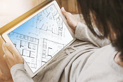Asian Guy Using Digital Tablet In Living Room, With Architectural Layout Plan On Screen Stock Photo