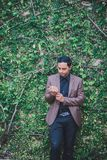 Asian guy wearing a brown suit on the wall are trees. Royalty Free Stock Photos